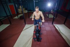Fit young man using exercise bike at the gym. Fitness male using air bike for cardio workout at cross training gym. Fit young man using exercise bike at the gym Stock Photo