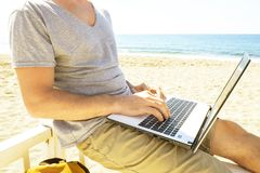 Young man in grey shirt sitting at the beach, working on laptop. royalty free stock photography