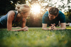 Fit young man and woman exercising in park Stock Images