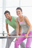 Fit young man and woman lifting barbells Stock Image