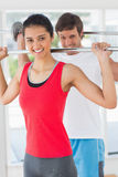 Fit young man and woman lifting barbells Stock Photos