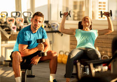 Fit young man and woman lifting dumbbells at the modern gym. Fitness trainig gym weight lifting bar by women and men group workout Stock Photography