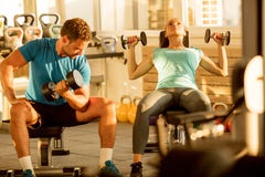 Fit young man and woman lifting dumbbells at the modern gym. Fitness trainig gym weight lifting bar by women and men group workout Stock Photo