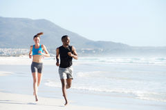 Fit young man and woman running along the beach Royalty Free Stock Image