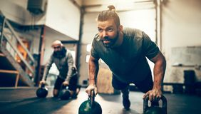 Fit man doing pushups with weights on a gym floor royalty free stock photo