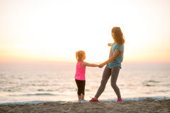 Fit young mother and daughter on the beach, looking out to sea Stock Images