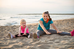 Fit young mother and daughter sitting on beach stretching Stock Image