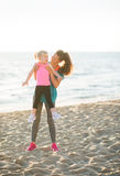 Fit young mother lifting young daughter up on beach at sunset Royalty Free Stock Photo