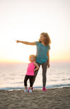 Fit young mother pointing into distance for daughter on beach. Her young daughter leaning up against her legs, a fit, happy mother points into the distance to Stock Photo