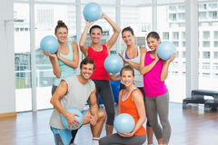 Fit young people with balls in exercise room Royalty Free Stock Photo