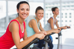 Fit young people working out at spinning class Stock Image