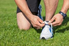 Fit young sportsman is tying his shoelaces. Close up of male legs kneeling. The athlete ties the laces on green grass Royalty Free Stock Image