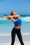 Fit young sporty woman stretching at the beach Stock Photo