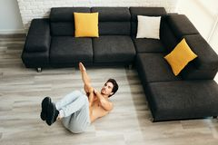 Adult Man Training ABS Muscles At Home Doing One Arm Crunches stock photo