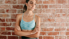 Fit young woman against brick wall. Portrait of fit young woman in sports bra standing against brick wall with her arms crossed. Caucasian female fitness model royalty free stock images