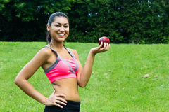 Fit young woman with an apple in the park Royalty Free Stock Photo