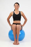 Fit young woman balancing on blue exercise ball Stock Image