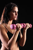 Fit young woman bicep curls with exercise weights Royalty Free Stock Images