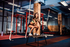 Fit young woman box jumping at a crossfit style. Royalty Free Stock Image