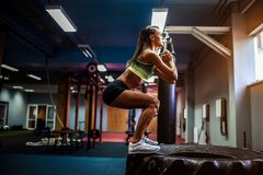 Fit young woman box jumping at a crossfit style. Fit young woman jumping on tire at a crossfit style gym. Female athlete is performing jumps stock photo