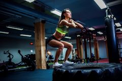 Fit young woman box jumping at a crossfit style. Fit young woman jumping on tire at a crossfit style gym. Female athlete is performing jumps royalty free stock images