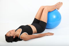 Fit young woman concentrating using exercise ball Royalty Free Stock Photo