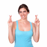 Fit young woman crossing her fingers Stock Photo