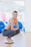 Fit young woman crouching on scale in exercise room Royalty Free Stock Photos