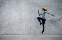 Fit young woman doing cardio interval training. Side view shot of fit young woman doing cardio interval training against grey background. Fitness female Stock Photo