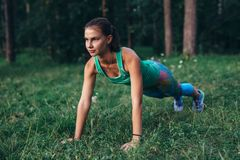 Fit young woman doing push-up exercise on grass in forest royalty free stock images
