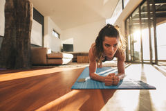 Fit young woman doing push ups at home Stock Image