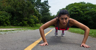 Fit young woman doing push-ups outdoors Stock Image