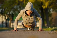 Fit young woman doing push ups outdoors Stock Photography
