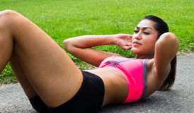 Fit young woman doing sit-ups outdoors Stock Photo