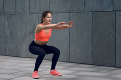 Fit young woman doing squats Stock Photos
