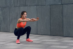 Fit young woman doing squats royalty free stock images