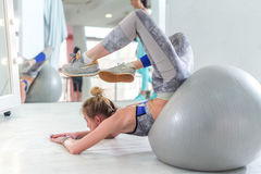Fit young woman doing stretching exercise for back on fitness ball lying trying to reach head with feet in sports club royalty free stock photography