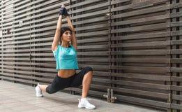 Fit young woman doing yoga stretching exercise, low lunge asana Anjaneyasana pose, outdoors. Fit young woman doing yoga stretching exercise, low lunge asana stock photography