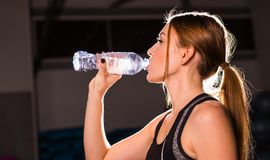Fitness young woman drinking water in the gym. Muscular woman taking break after exercise royalty free stock image