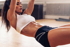 Fit young woman exercising at gym Stock Images