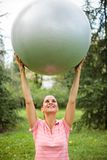 Fit young woman exercising, holding fitness ball high above her head stock image