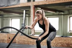 Free Fit Young Woman Exercising With Ropes At The Gym Stock Photography - 116437602