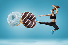 Fit young woman fighting off bad food on a blue background. Concept of diet and healthy lifestile Royalty Free Stock Images