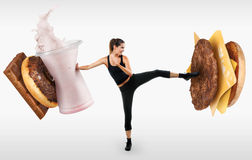 Fit young woman fighting off fast food. On gray background Stock Photo