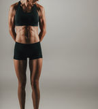 Fit young woman flexing her abdominal muscles Royalty Free Stock Photos