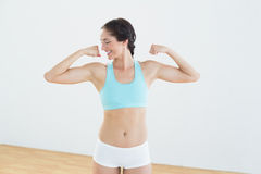 Fit young woman flexing muscles. In fitness studio Royalty Free Stock Images
