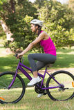 Fit young woman with helmet riding bicycle at park Stock Photo