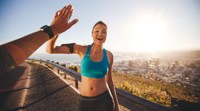 Fit young woman high fiving her boyfriend after a run. Fit young women high fiving her boyfriend after a run. POV shot of runners on country road looking happy Stock Photography