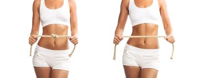 Fit young woman holding a tied and untied rope over her abdomen, on white background Royalty Free Stock Image