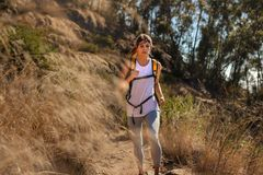 Fit young woman with hydration pack running over a hill. Female athlete running through mountain trail stock photography